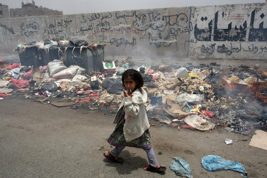 A Yemeni girl gestures as she walks past