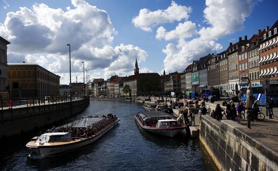 People enjoy the sunshine near a canal i