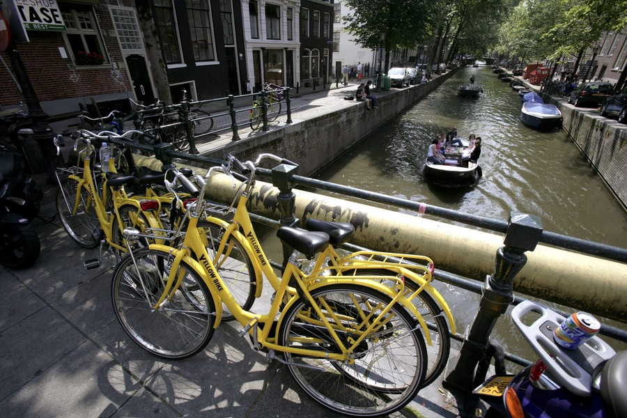 NETHERLANDS, AMSTERDAM, Yellow Bike rented bikes in front of the Keizersgracht ( Emperors Canal) with boats in Amsterdam.
