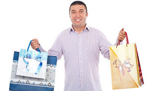 Buyer man holding shopping bags and smiling isolated on white background